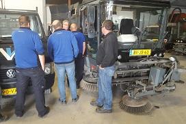 Medewerkers bij een straatveegmachine in een garage.