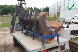 Een graafbak vastgesjord op een aanhangwagen voordat deze wordt verplaatst.